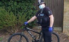 Policeman next to a bike