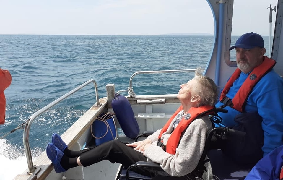 woman in a wheelchair and a man on a boat