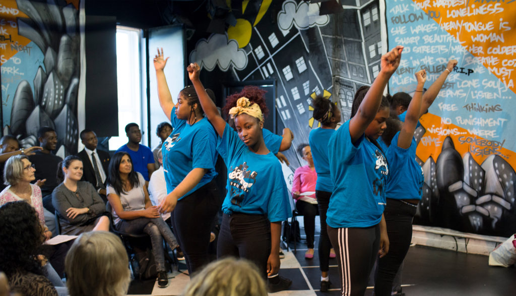 A group of children with their hands in the air from SW Youth Arts