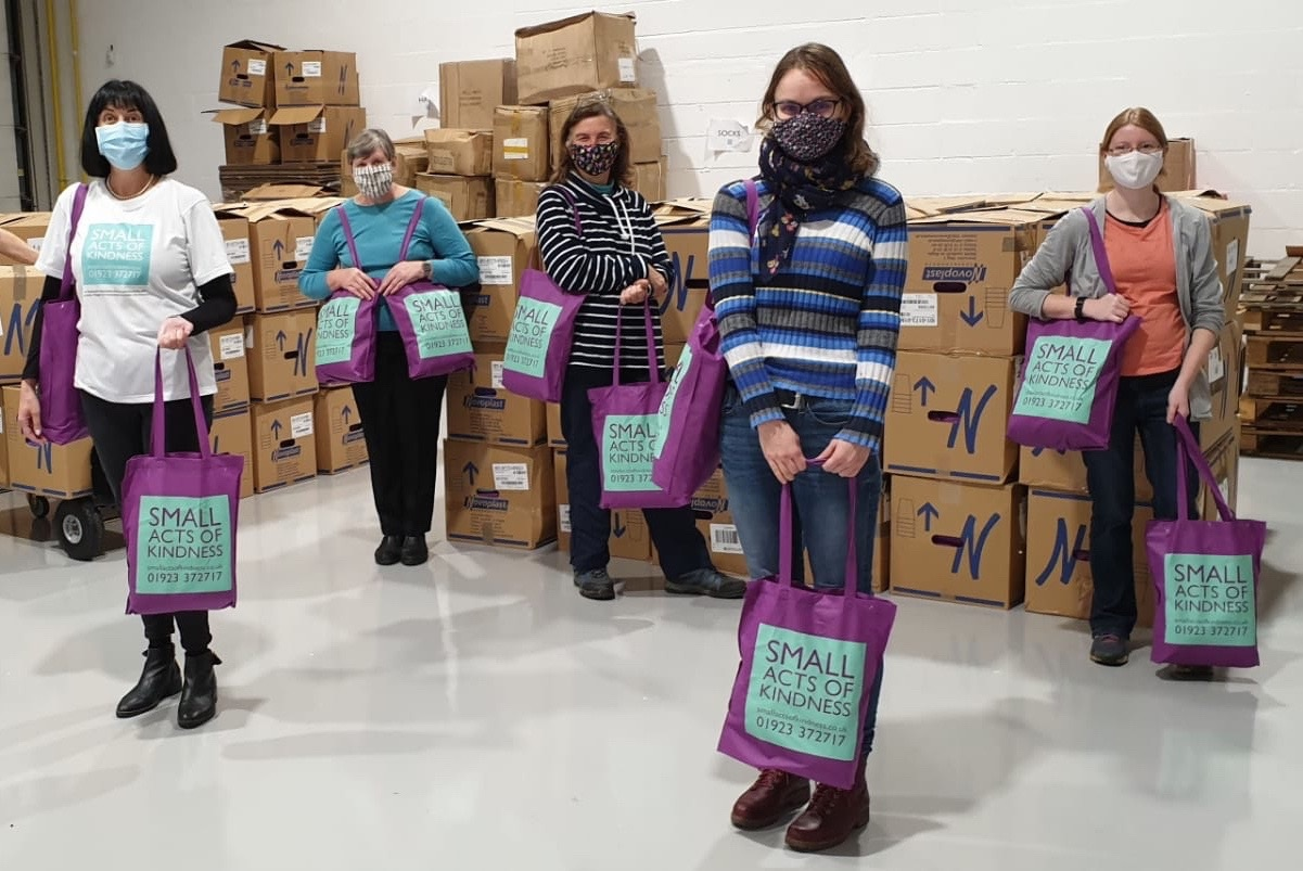 People standing apart holding small acts of kindness bags