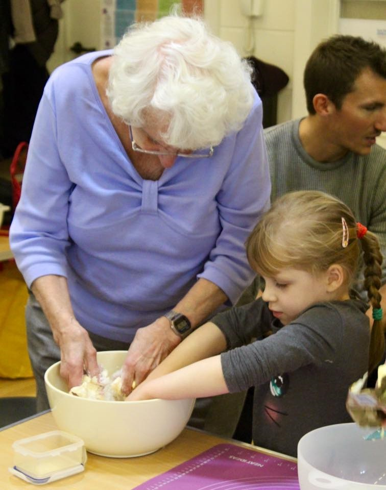 An elderly lady baking with a child