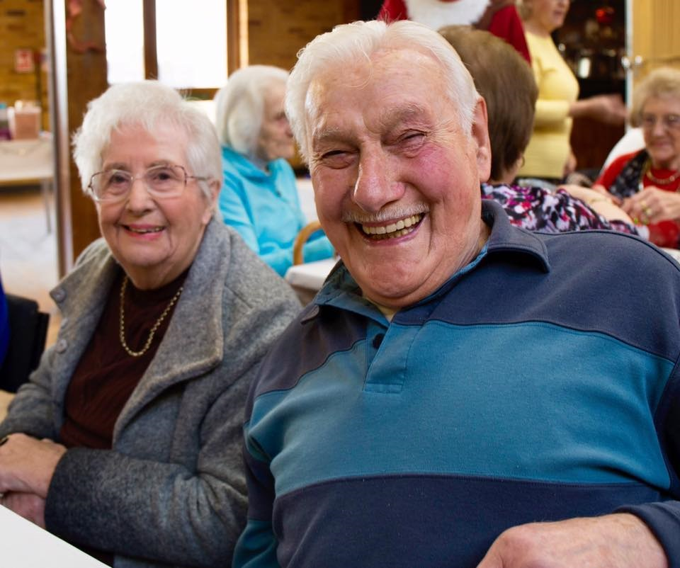 Two elderly people smiling for a photo