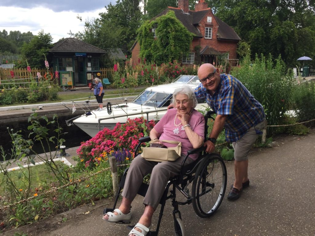 A man pushing a lady on a wheelchair by the canal