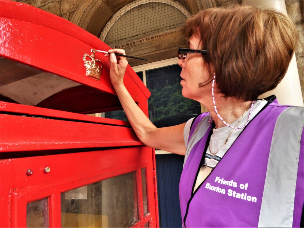 Sue Mellor painting gold crown on red rescued telephone box