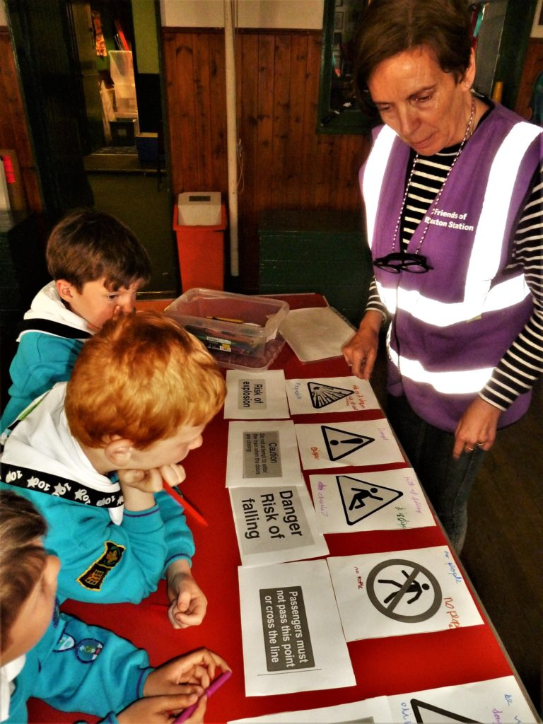 A woman stood next to a table with different saftey signs, children in scouting uniforms looking at the signs