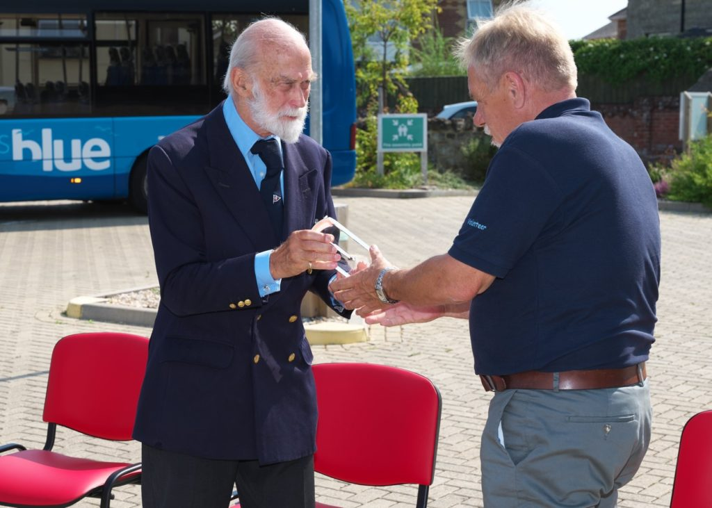 His Royal Highness Prince Michael of Kent presents QAVS crystal to volunteer of the Isle of Wight Bus Partnership