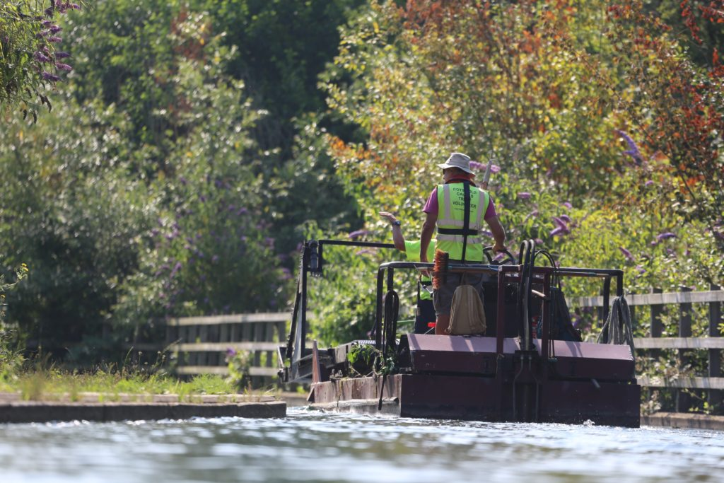 Volunteer in a high-visability jacket on a boat in the canal, clearing debry. Lots of trees surround the canal.