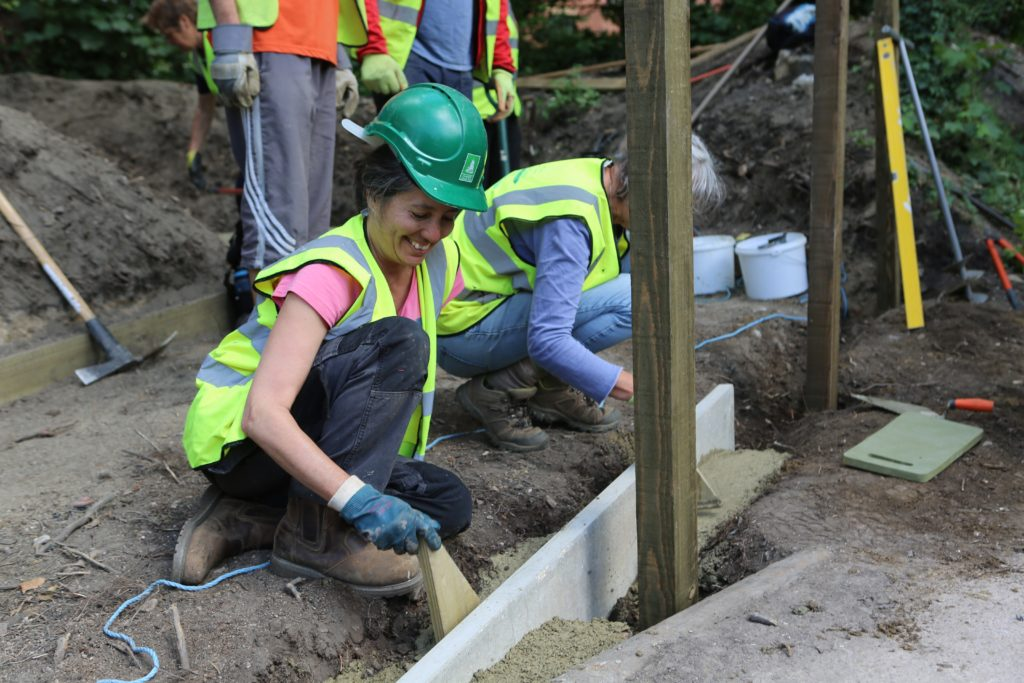 Volunteer smiles as she builds the foundation of a pontoon. She wears a hard hat and high-vis jacket.