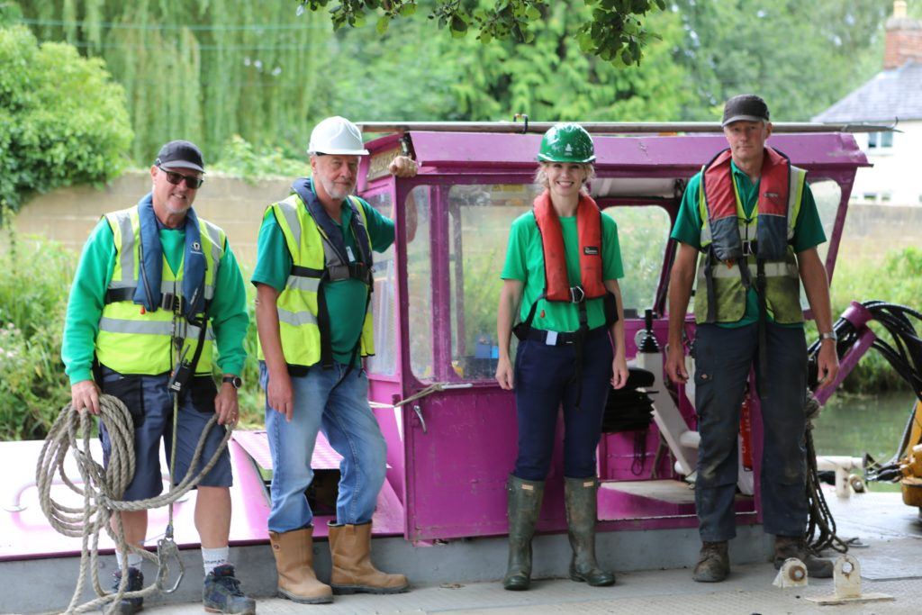 Four volunteers stood smiling in front of a purple canal boat.