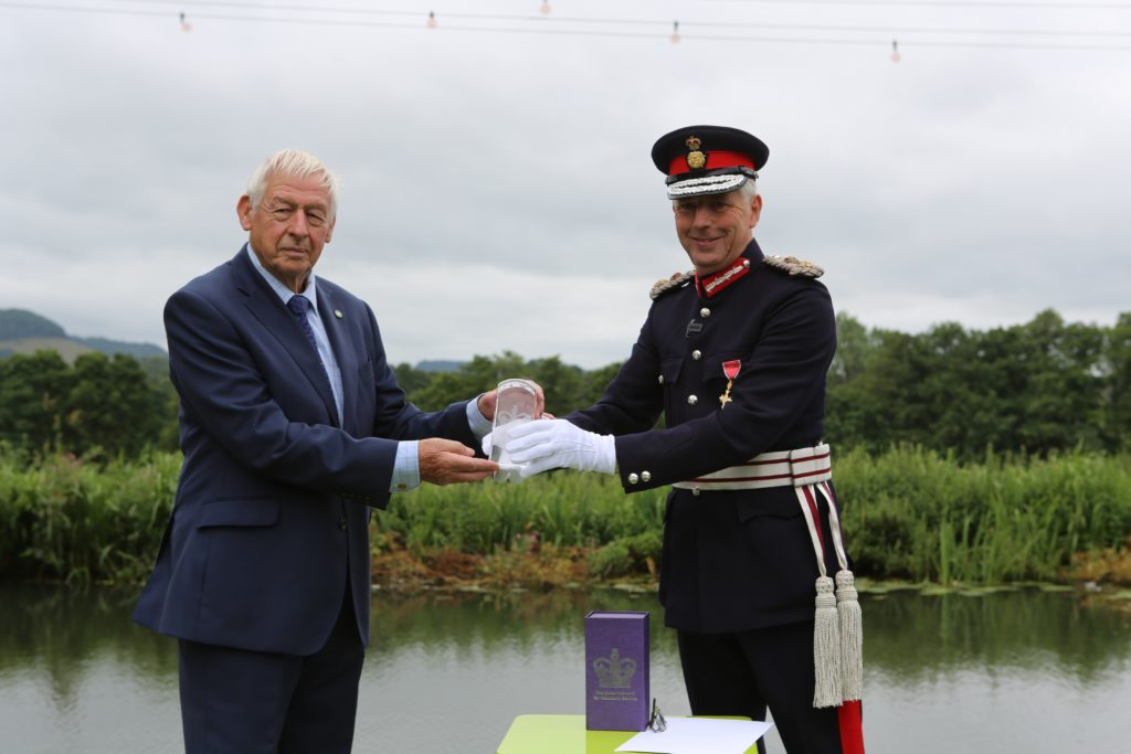 The Lord-Lieutenant hands the QAVS award crystal to a representative of The Cotswold Canals Trust