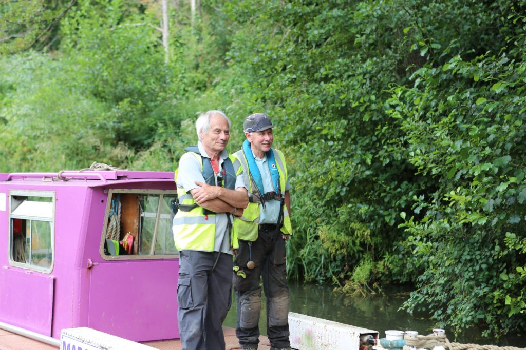 two male volunteers stood smiling on a canal boat while it travels down the canal.