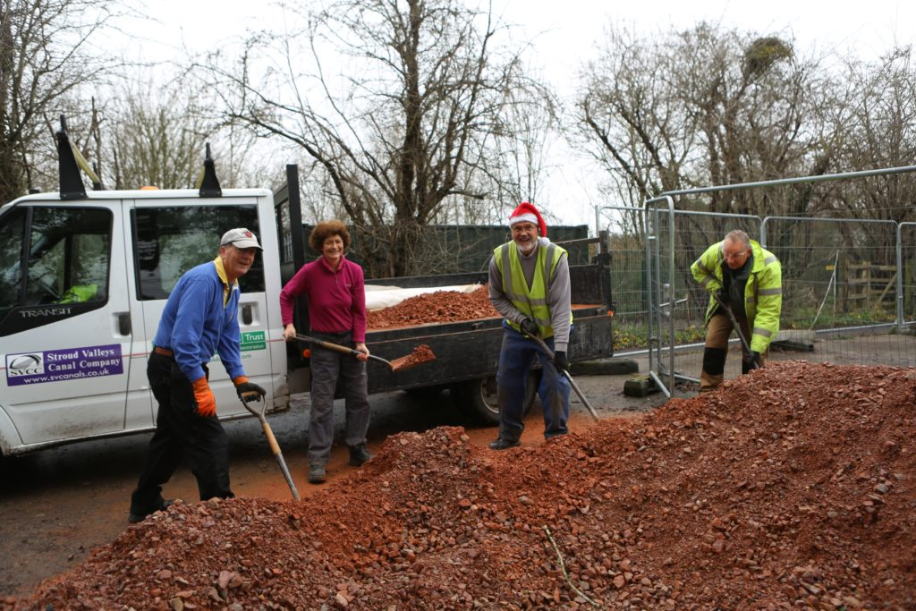 Four volunteers pictured shoveling gravel onto a truck.
