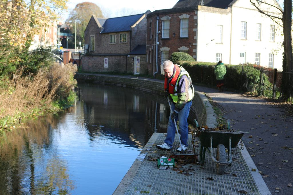 Pictured is a male volunteer in life-jacket and high visability clothing. He is sweeping up litter next to the canal. There is a wheelbarrow next to his right.