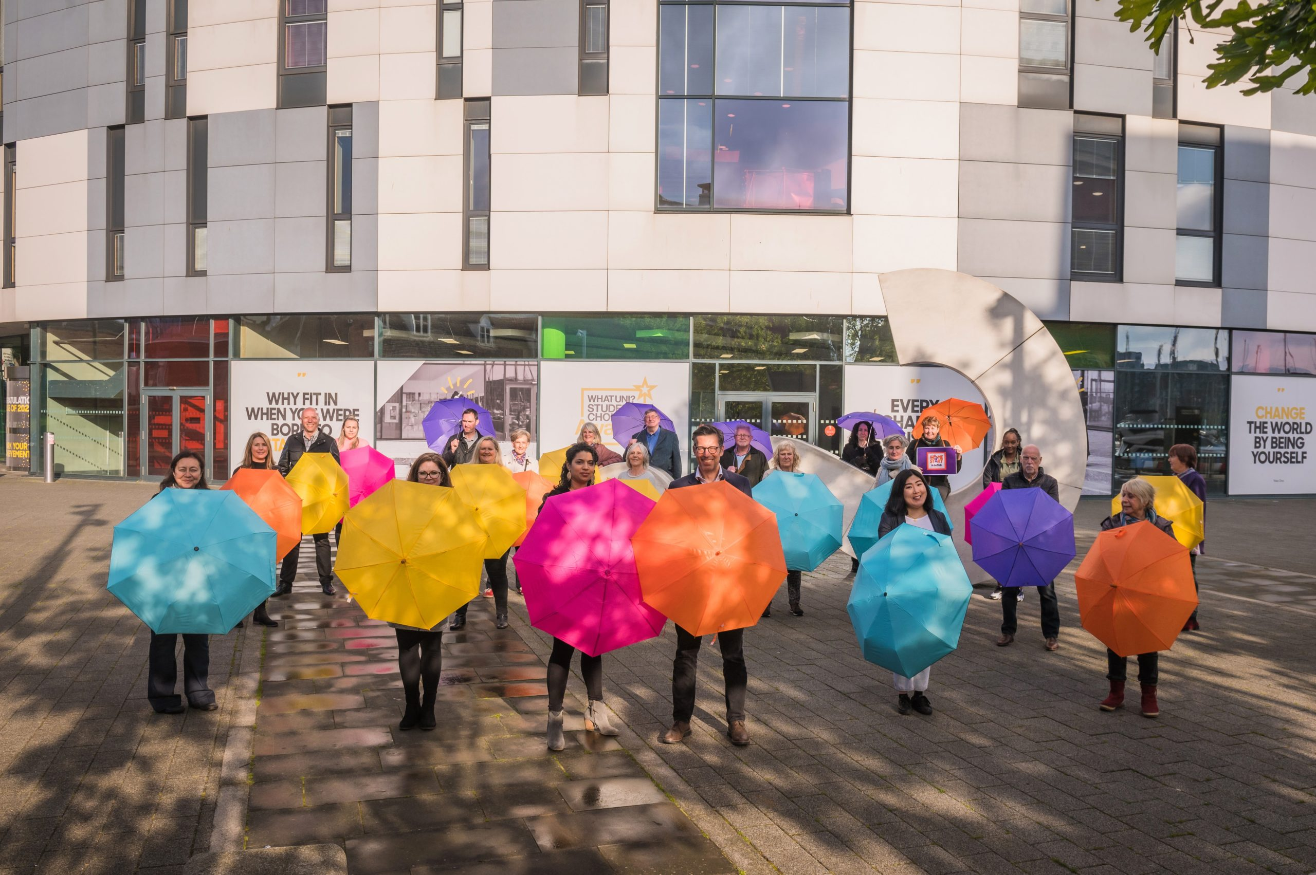 A group of people stood holding colourful umbrella's